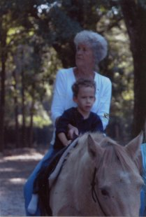 Young child riding horse while being held by an adult.